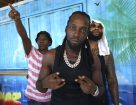 """Mavado (C), Jamaican dancehall star, joined in the street festivities in Roseau, October 26., 2018 in Roseau, Dominica. - Amid the kaleidoscope of colors of Dominica's capital Roseau, the streets pulsated with the sounds of African drums and steelpans, bamboo """"boom pipes"""" and accordions. Impromptu parties sprung up on roadsides and beaches for the weekend of revelry that is the World Creole Music Festival, a chance to showcase the origins of the now global but intrinsically Caribbean sound. The 20th edition of the festival brought thousands from across the Caribbean to the tiny island nation and sent a message that Dominica has moved on from Hurricane Maria, which last year claimed dozens of lives here as it obliterated homes and livelihoods. (Photo by Gemma HANDY / AFP) (Photo credit should read GEMMA HANDY/AFP/Getty Images)"""